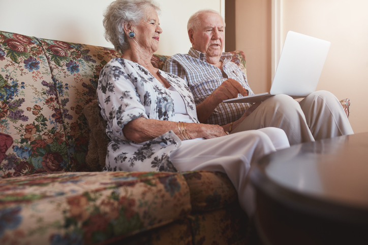 Elderly couple relaxing on sofa and using laptop